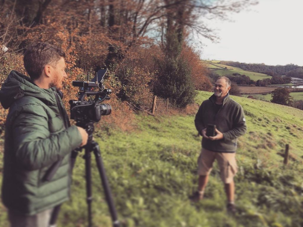 Location matters when you're trying to make better videos. If you're outside, keep your subject's back to the wind to reduce wind noise. Here, Ross was filming a client outdoors in a green field with autumnal trees.