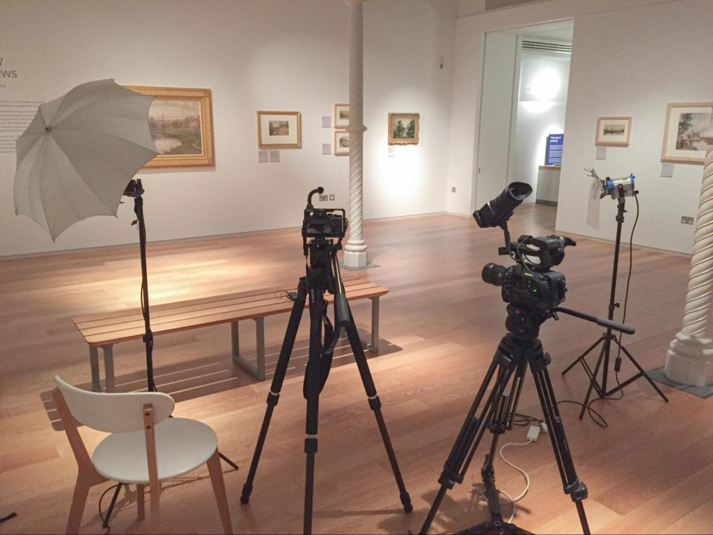 Make better video with appropriate kit. This is an image of two cameras and professional lighting in a gallery.